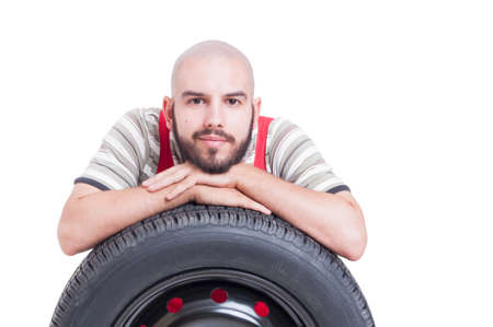 leans on hand: Kind and friendly young mechanic resting on car wheel tire isolated on white Stock Photo