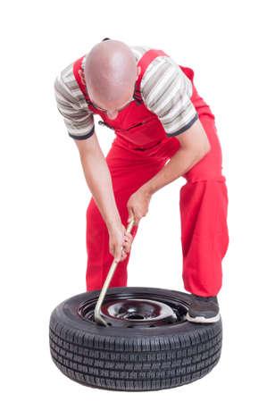 hardworking: Hard-working mechanic changing car wheel tire isolated on white