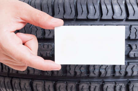recycle area: Hand holding blank card on car wheel tire background. Copy space, text area or logo spot concept Stock Photo