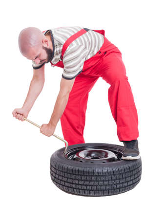 vulcanization: Busy vulcanization mechanic changing car tire isolated on white Stock Photo