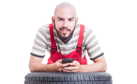 leans on hand: Mechanic holding smartphone and texting resting on wheel tire