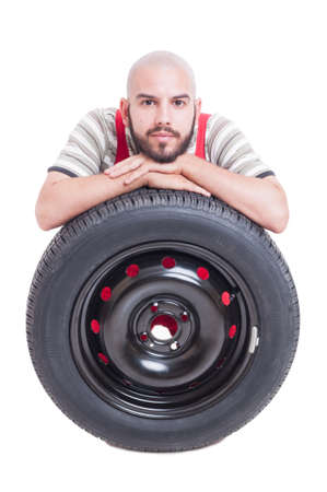 leans on hand: Mechanic and new car wheel tire isolated on white studio  background