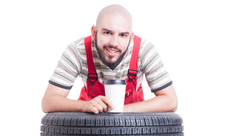 leans on hand: Mechanic taking a coffee break after work concept isolated on white