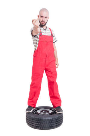 insulting: Mechanic standing on top of car wheel showing obscene insulting and offensive middle finger isolated on white