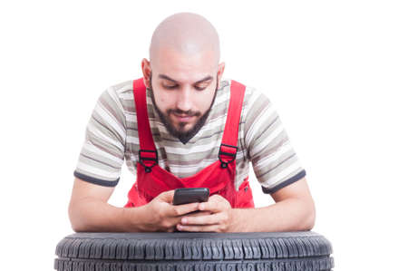 leans on hand: Mechanic having a break and using smartphone isolated on white Stock Photo