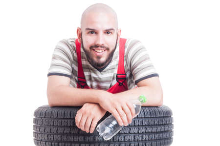 leans on hand: Smiling mechanic holding a bottle of water and resting on a car wheel Stock Photo