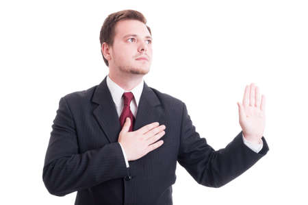 swearing: Lawyer making oath or swearing gesture with one hand on the heart and the other one up