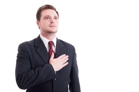 honestidad: Hombre de negocios orgulloso o un abogado de la celebraci�n de una mano en el coraz�n aislado en blanco