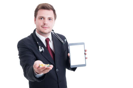 doctor holding pills: Modern doctor holding pills and white blank tablet screen with copy space