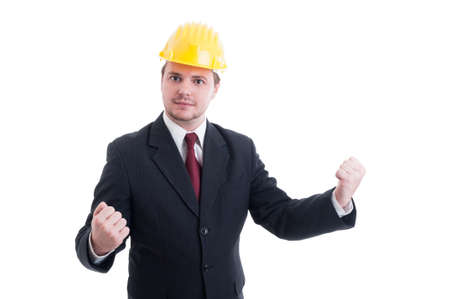 the victorious: Successful and victorious engineer, architect or contractor wearing suit, tie and yellow hardhat Stock Photo