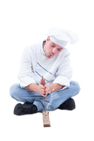 friction: Cook or chef making fire with stick and wood sitting isolated on white. Smoke starting on friction as manly surviving skills