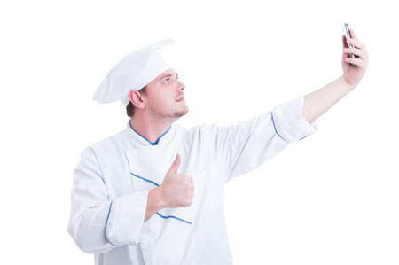 thumbup: Chef or cook taking selfie with phone camera showing like thumbup gesture