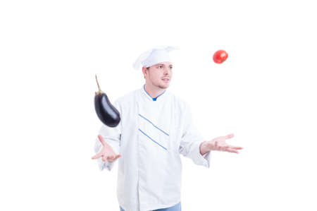 levitate: Chef or cook juggling with vegetables an eggpland and one tomato isolated on white studio background