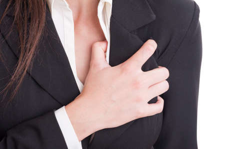 Heart attack or cardiac arrest gesture made by suited woman. Closeup with hand grabbing chest pain Reklamní fotografie