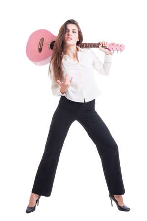 female devil: Sexy young and beautiful female or woman guitarist with rock attitude showing devil horns and holding an acoustic pink quitar Stock Photo