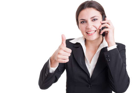 thumbup: Smiling happy business woman showing like or thumb-up gesture while having a phone conversation