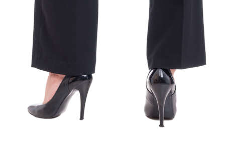 Business woman legs wearing black leather shoes with high heels isolated on white studio background