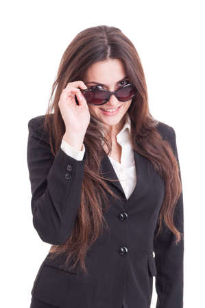 businesswoman suit: Young sexy and beautiful business woman looking over shades or sunglasses isolated on white background