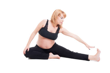 8 months pregnancy: Beautiful young pregnant woman stretching isolated on the white floor Stock Photo