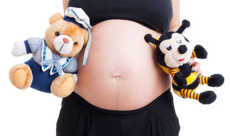 Closeup with big pregnant woman belly and cute plush toys on white background