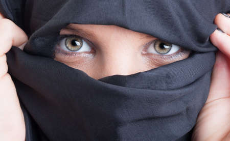 burka: Close-up with beautiful islamic woman eyes and face covered by black burka