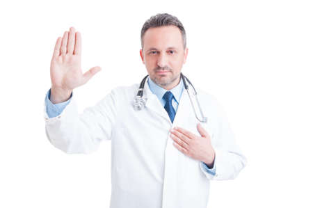 oath: Confident and trustworthy medic or doctor making Hippocratic oath with hand on heart isolated on white background
