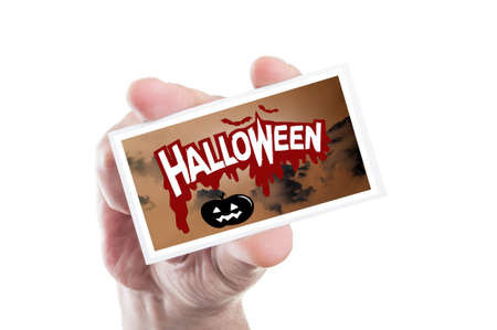 man holding card: Man hand holding spooky Halloween party card or invitation isolated on white background