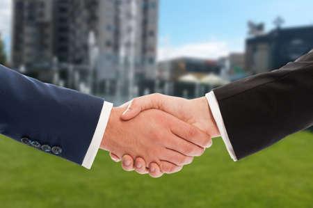 saludo de manos: Apretón de manos inmobiliaria sobre el edificio y la propiedad en venta fondo verde Foto de archivo