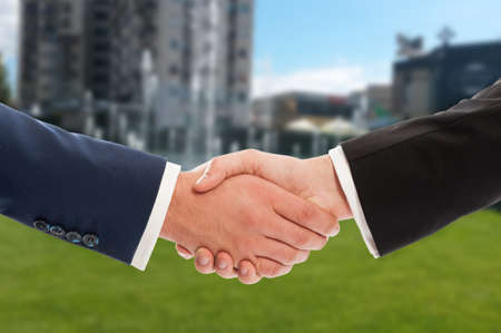 business and commerce: Real estate handshake over building and green property for sale background