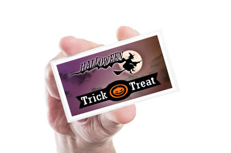 man holding card: Man hand holding scary Halloween party card or invitation isolated on white background
