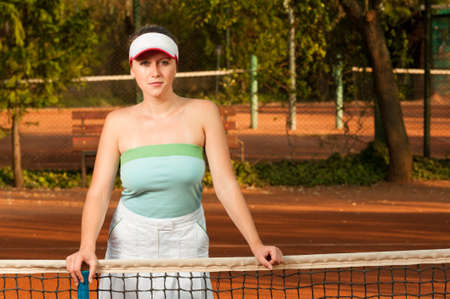 Woman tennis player holding racket near netting and posing outdoor on clay court Stock Photo