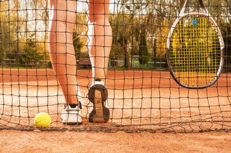 Tennis concept met bal, netten, racket en vrouw benen buiten op gravel Stockfoto
