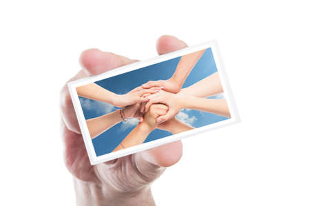manos unidas: Mano que sostiene la tarjeta de voluntarios con el fondo de las manos unidas como ONG de voluntariado concepto Foto de archivo