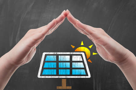 energy efficiency: Hand protecting solar power panel draw on blackboard as green energy concept Stock Photo