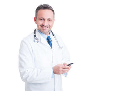 medic: Young and friendly doctor or medic texting on smartphone smiling to the camera isolated on white