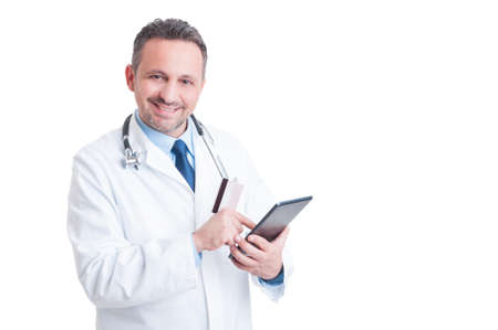 secure payment: Smiling doctor or medic using credit  card and wireless tablet  as online medical services secure payment concept Stock Photo