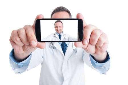 Handsome doctor or medic taking a selfie with back camera smiling isolated on white background Standard-Bild