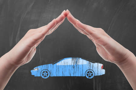 auto insurance: Hands protecting car shape as auto insurance concept illustrated on blackboard Stock Photo