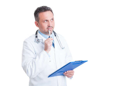 Handsome doctor or medic holding clipboard and thinking isolated on white background Reklamní fotografie