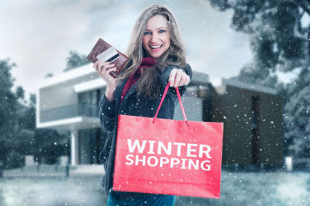 Winter shopping woman concept with snowing outdoor background Standard-Bild