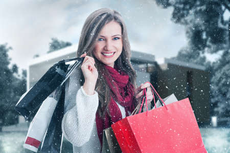 Winter shopping woman smiling outdoor and carrying gift bags