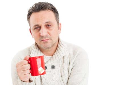 Hombre enfermo con la cara triste sufrimiento de los virus de la gripe que sostiene una taza de té caliente