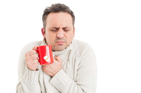 shivering: Cold man holding tea mug and shivering or freezing while suffering of influenza