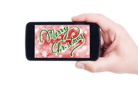 hand held: Merry Christmas concept on phone display held by hand