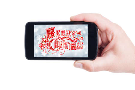 hand held: Merry Christmas concept on smartphone screen held by hand
