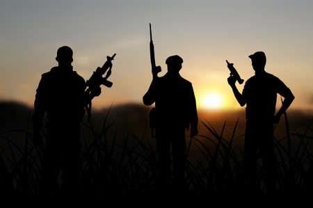 iraq conflict: Terrorist or terrorism concept with silhouettes on sunset background Stock Photo