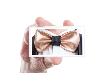 hand holding card: Hand holding card with golden leather bowtie picture as bow tie fashion concept