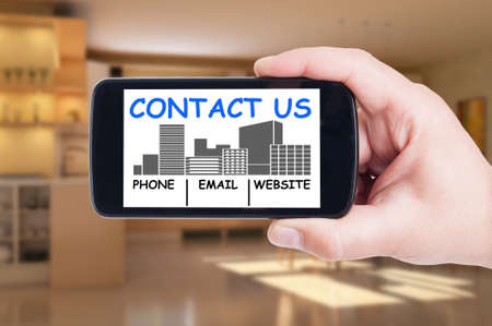 Contact real estate agency concept with mobile phone, smartphone or cellphone and email and website address details