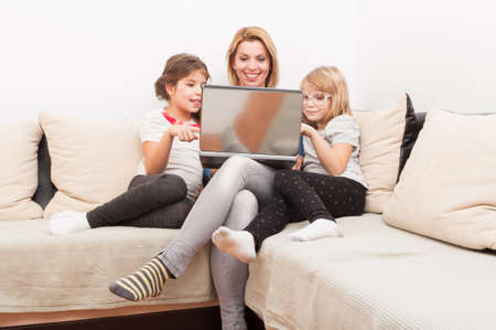 family sofa: Family surfing or browsing internet together using laptop relaxed on the sofa or couch