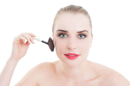 skintone: Portrait of woman applying cosmetics with brush isolated on white background